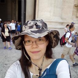 Portrait of Limin Xu wearing a wide-brimmed hat